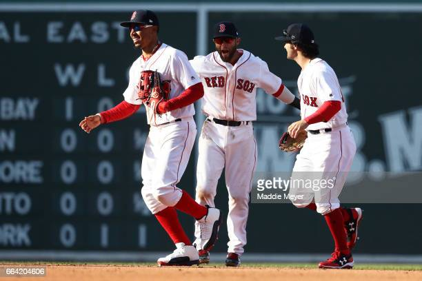 Mookie Betts of the Boston Red Sox celebrates with Dustin Pedroia and Andrew Benintendi after defeating the Pittsburgh Pirates 53 in the opening day...