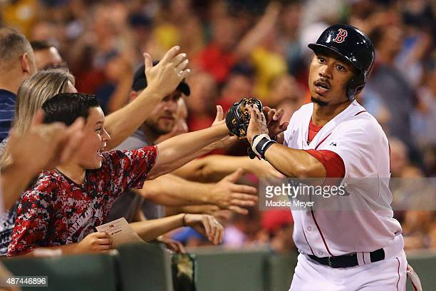 Mookie Betts of the Boston Red Sox celebrates with fans after hitting a solo home run during the third inning against the Toronto Blue Jays at Fenway...