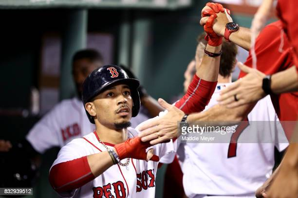 Mookie Betts of the Boston Red Sox celebrates with teammates in the dugout after scoring a run against the St Louis Cardinals during the third inning...