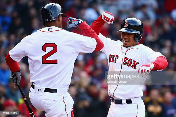 Mookie Betts of the Boston Red Sox celebrates with Xander Bogaerts of the Boston Red Sox after hitting a home run during the ninth inning of the Red...