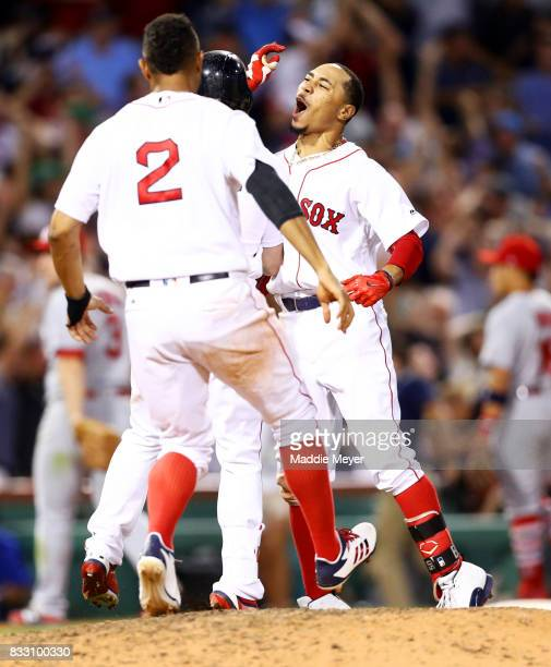 Mookie Betts of the Boston Red Sox celebrates with Xander Bogaerts after hitting a go ahead two run double to defeat the St Louis Cardinals 54 at...