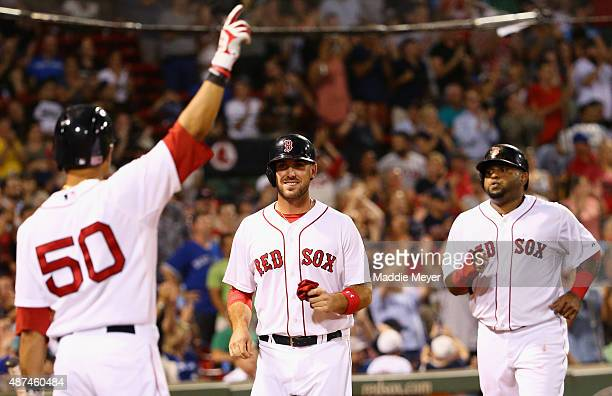 Mookie Betts of the Boston Red Sox congratulates Travis Shaw and Pablo Sandoval after they scored runs against the Toronto Blue Jays during the fifth...