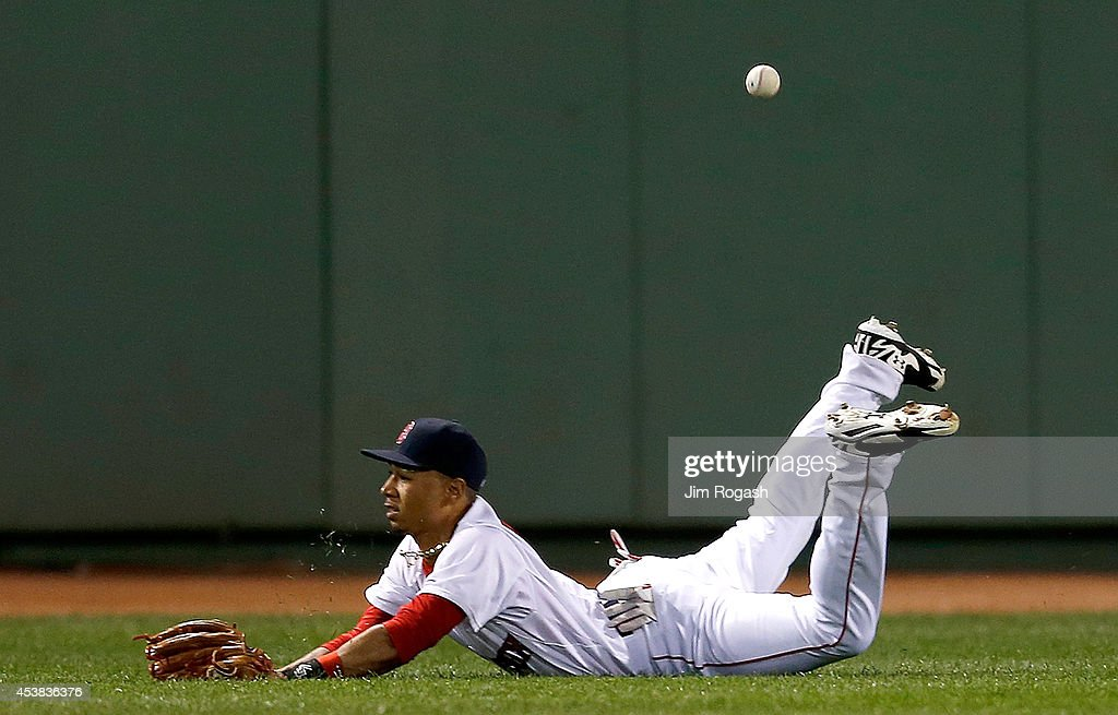 Mookie Betts #50 of the Boston Red Sox dives for a ball hit by David Freese #6 of the Los Angeles Angels of Anaheim in the fourth inning at Fenway Park on August 19, 2014 in Boston, Massachusetts.