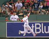 Mookie Betts of the Boston Red Sox falls over the outfield wall and into the bullpen after catching a ball hit by Jose Abreu of the Chicago White Sox...
