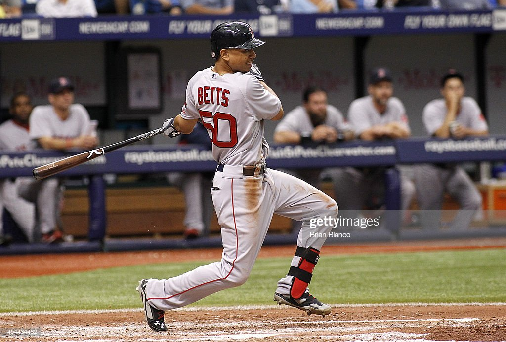 Mookie Betts #50 of the Boston Red Sox follows through as he hits a one-run single to score Brock Holt during the fifth inning of a game against the Tampa Bay Rays on August 31, 2014 at Tropicana Field in St. Petersburg, Florida.