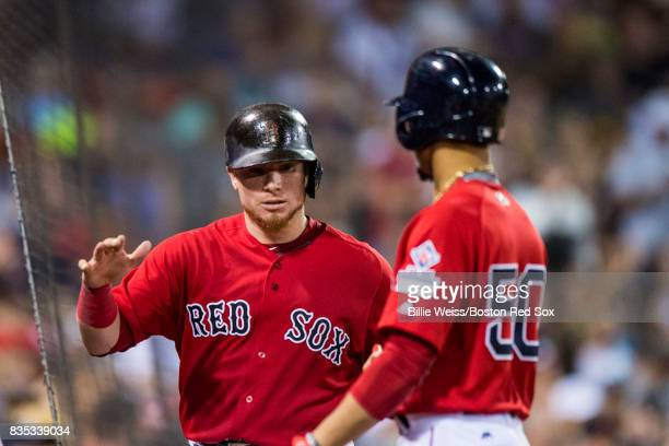 Mookie Betts of the Boston Red Sox high fives Christian Vazquez after hitting a sacrifice fly to drive him in during the seventh inning of a game...