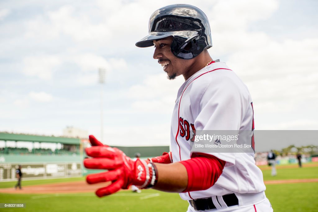 Mookie Betts #50 of the Boston Red Sox high fives teammates after scoring during the first inning of a Spring Training game against the Atlanta Braves on March 5, 2017 at Fenway South in Fort Myers, Florida .