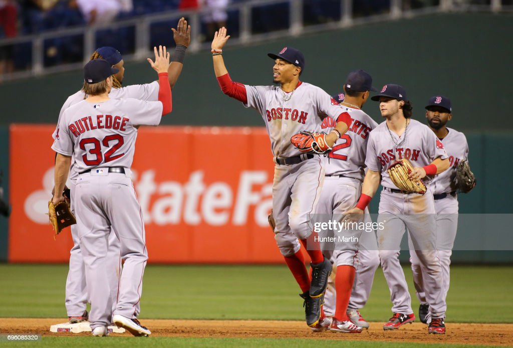Mookie Betts #50 of the Boston Red Sox high fives teammates after winning a game against the Philadelphia Phillies at Citizens Bank Park on June 14, 2017 in Philadelphia, Pennsylvania. The Red Sox won 7-3.