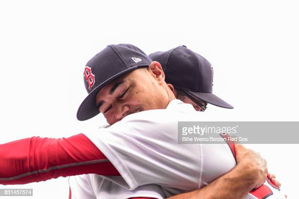 Mookie Betts of the Boston Red Sox hugs first base coach Ruben Amaro Jr before a game against the Cleveland Indians on August 14 2017 at Fenway Park...