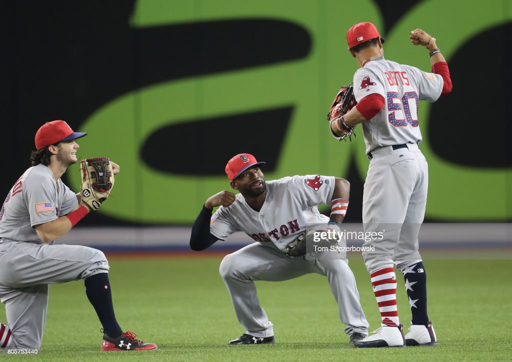 Mookie Betts #50 of the Boston Red Sox is congratulated by Andrew Benintendi #16 and Jackie Bradley Jr. #19 after their victory during MLB game action against the Toronto Blue Jays at Rogers Centre on July 2, 2017 in Toronto, Canada.