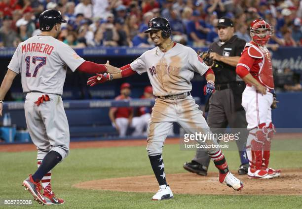 Mookie Betts of the Boston Red Sox is congratulated by Deven Marrero after hitting a threerun home run in the fourth inning during MLB game action...