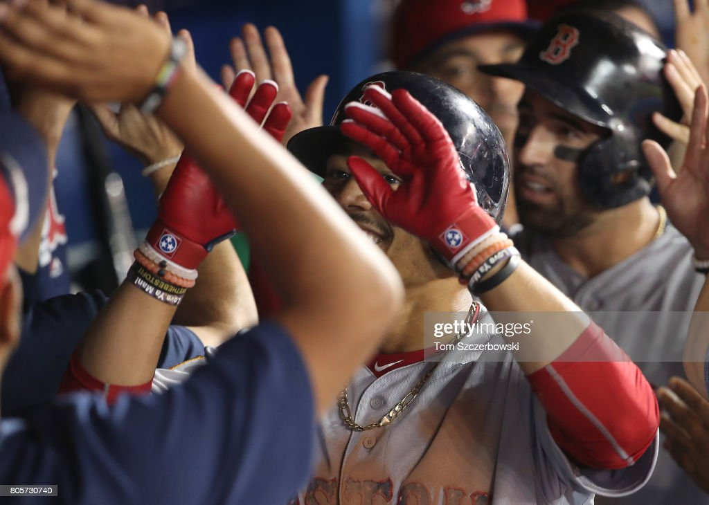 Mookie Betts #50 of the Boston Red Sox is congratulated by teammates in the dugout after hitting a two-run home run in the sixth inning during MLB game action against the Toronto Blue Jays at Rogers Centre on July 2, 2017 in Toronto, Canada.