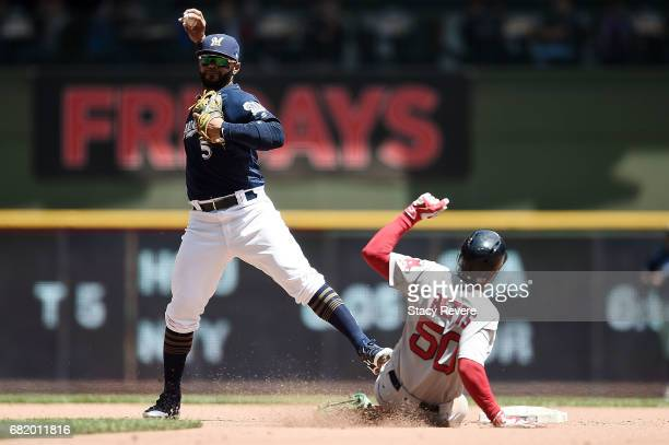 Mookie Betts of the Boston Red Sox is forced out at second base as Jonathan Villar of the Milwaukee Brewers makes a throw to first base during the...
