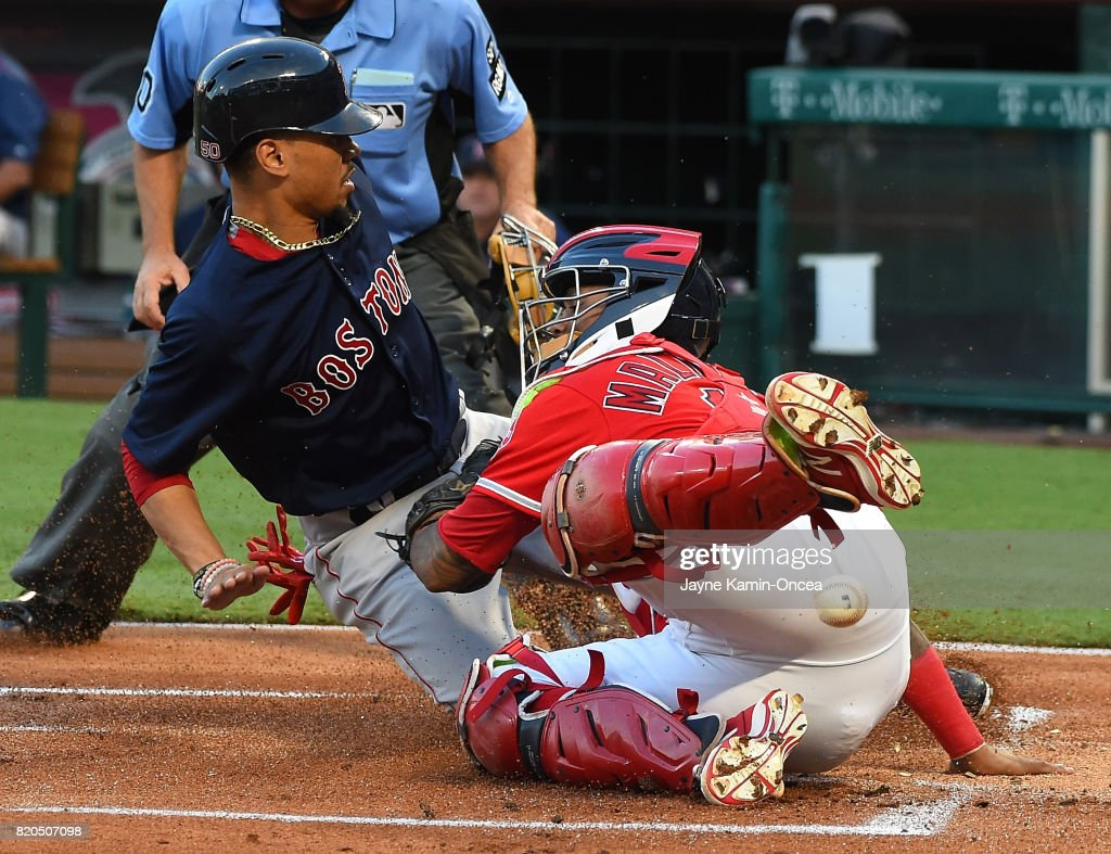 Mookie Betts #50 of the Boston Red Sox is safe at home scoring the first run of the game as the ball pops out of the glove of Martin Maldonado #12 of the Los Angeles Angels of Anaheim at Angel Stadium of Anaheim on July 21, 2017 in Anaheim, California.