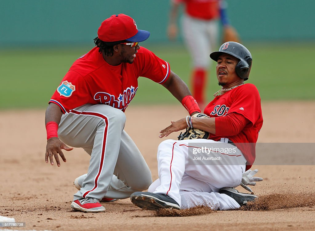 Mookie Betts #50 of the Boston Red Sox is tagged out at third base by Maikel Franco #7 of the Philadelphia Phillies during the fourth inning of a spring training game at JetBlue Park on March 27, 2016 in Fort Myers, Florida. The Red Sox defeated the Phillies 5-1.