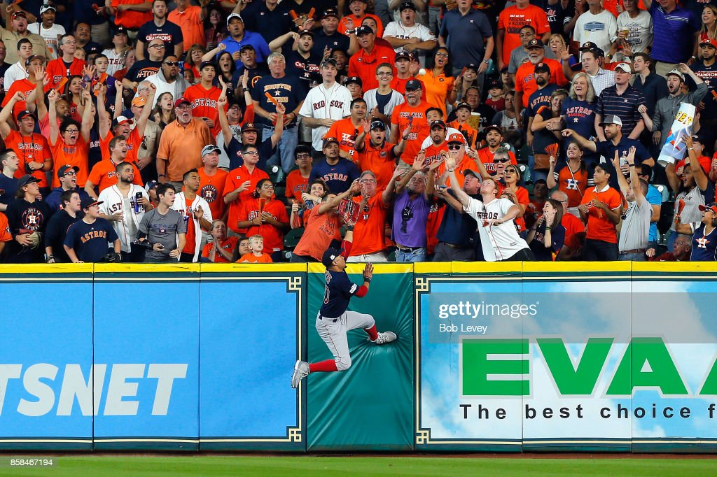 Mookie Betts #50 of the Boston Red Sox is unable to catch a home run ball hit by George Springer #4 of the Houston Astros (not pictured) in the third inning during game two of the American League Division Series at Minute Maid Park on October 6, 2017 in Houston, Texas.