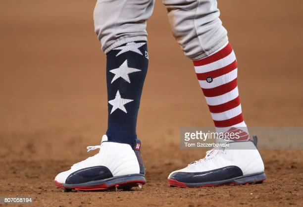 Mookie Betts of the Boston Red Sox leads off first base as he wears socks with the stars and stripes design in the seventh inning during MLB game...