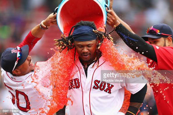 Mookie Betts of the Boston Red Sox left and Eduardo Rodriguez dump red Powerade on Hanley Ramirez of the Boston Red Sox after defeating the Tampa Bay...