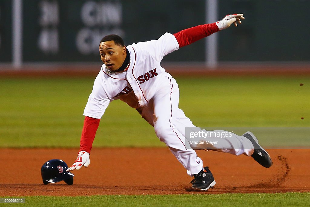 Mookie Betts #50 of the Boston Red Sox loses his helmet running between second and third during the first inning against the Baltimore Orioles at Fenway Park on April 13, 2016 in Boston, Massachusetts.