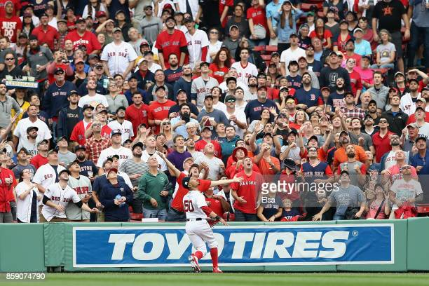 Mookie Betts of the Boston Red Sox prepares to catch a ball hit by Josh Reddick of the Houston Astros in the second inning during game three of the...