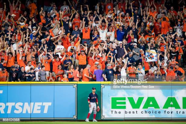 Mookie Betts of the Boston Red Sox reacts after attempting to catch a solo home run hit by George Springer of the Houston Astros during the third...