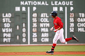 Mookie Betts of the Boston Red Sox rounds the bases after hitting a home run against the Minnesota Twins during the first inning at Fenway Park on...
