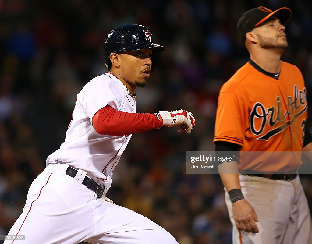 Mookie Betts #50 of the Boston Red Sox runs out his rbi producing ground-rule double as Steve Pearce #28 of the Baltimore Orioles reacts at first base in the eighth inning at Fenway Park on September 26, 2015 in Boston, Massachusetts.