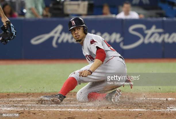 Mookie Betts of the Boston Red Sox slides across home plate as he is forced out with the bases loaded in the seventh inning during MLB game action...