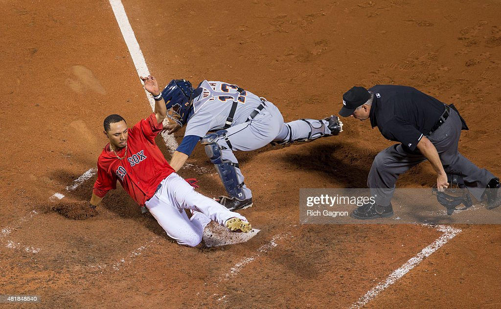 Mookie Betts of the Boston Red Sox slides as he avoids the tag by Alex Avila of the Detroit Tigers at home plate as he scored the winning run during...