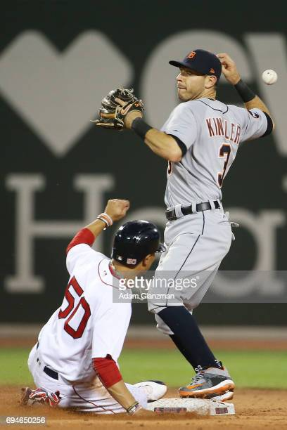 Mookie Betts of the Boston Red Sox slides into second base as Ian Kinsler of the Detroit Tigers bobbles the ball in the fifth inning of a game...