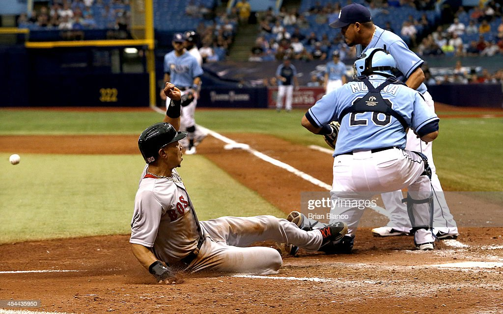 Mookie Betts #50 of the Boston Red Sox slides safely into home plate headed of catcher Jose Molina #28 of the Tampa Bay Rays and pitcher Joel Peralta #62 to score off of a single by David Ortiz during the eighth inning of a game on August 31, 2014 at Tropicana Field in St. Petersburg, Florida.