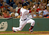 Mookie Betts of the Boston Red Sox starts his swing as he double in three runs in the second inning against the Cleveland Indians at Fenway Park on...