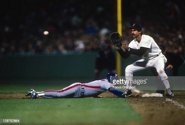 Mookie Wilson of the New York Mets dives back beating the throw over to first baseman Bill Buckner of the Boston Red Sox in the 1986 world series in...