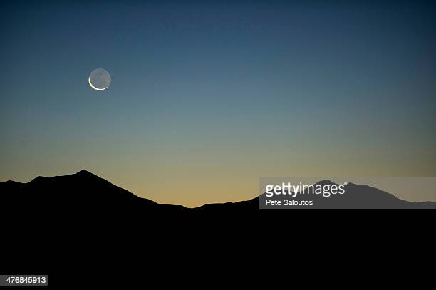 Moon and mountains in silhouette, Moab, Utah, USA