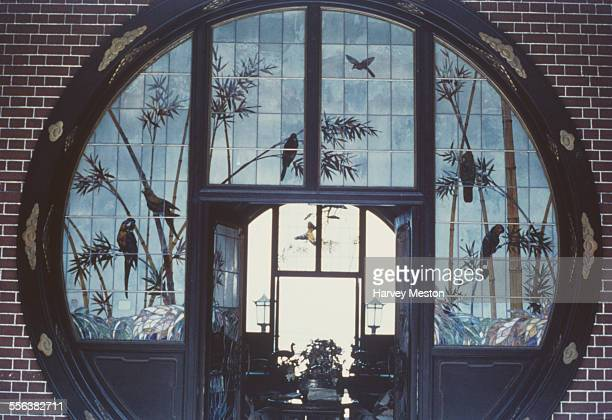 A moon gate decorated with stained glass images of birds in Hong Kong circa 1965