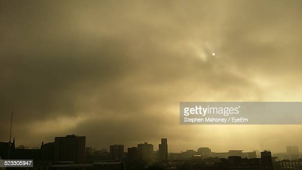 Moon In Cloudy Sky Over City