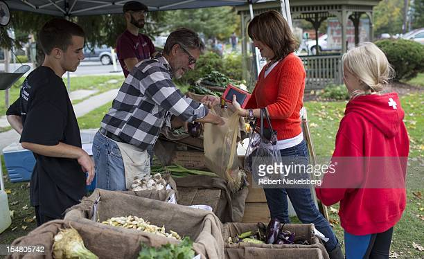 Moon in the Pond farm owner Dominic Palumbo center left puts organically grown eggplants in a woman's bag October 6 2012 at the weekly farmers'...
