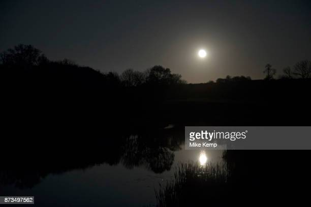 Moon in the sky above the lake in the grounds of stately home Compton Verney in Kineton United Kingdom Compton Verney House is an 18thcentury country...
