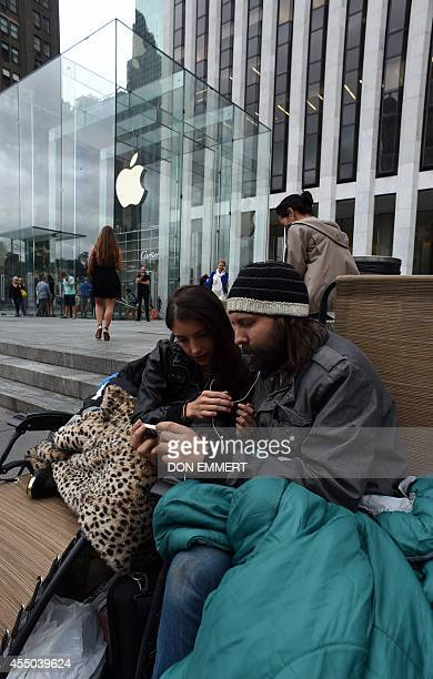 Moon Ray and her husband Jason Ray talk on skype as they wait in line September 9 2014 outside the Apple Store on 5th Avenue in New York Tech...