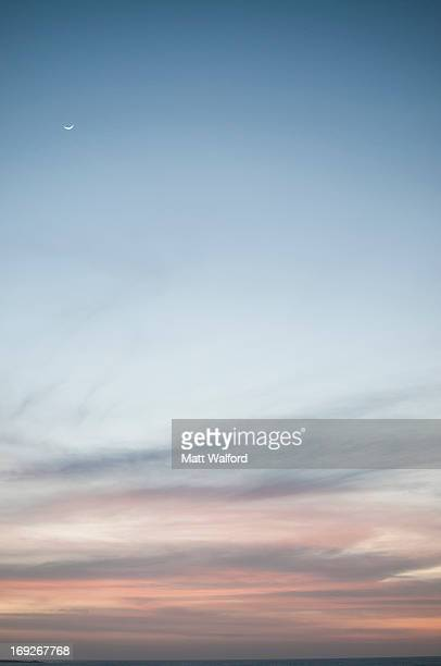 Moon rising over colorful sky