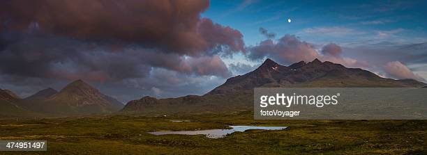 Moon rising over epic mountain landscape stormy sunset panorama Scotland
