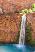 Mooney Falls plunges 200 feet into a deep blue-green pool surrounded by red travertine cliffs on the Havasupai Indian Reservation in the Grand Canyon.
