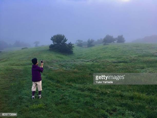 Moonlight Blues - Japanese Senior Woman Photographing Foggy Landscape with Smart Phone Device