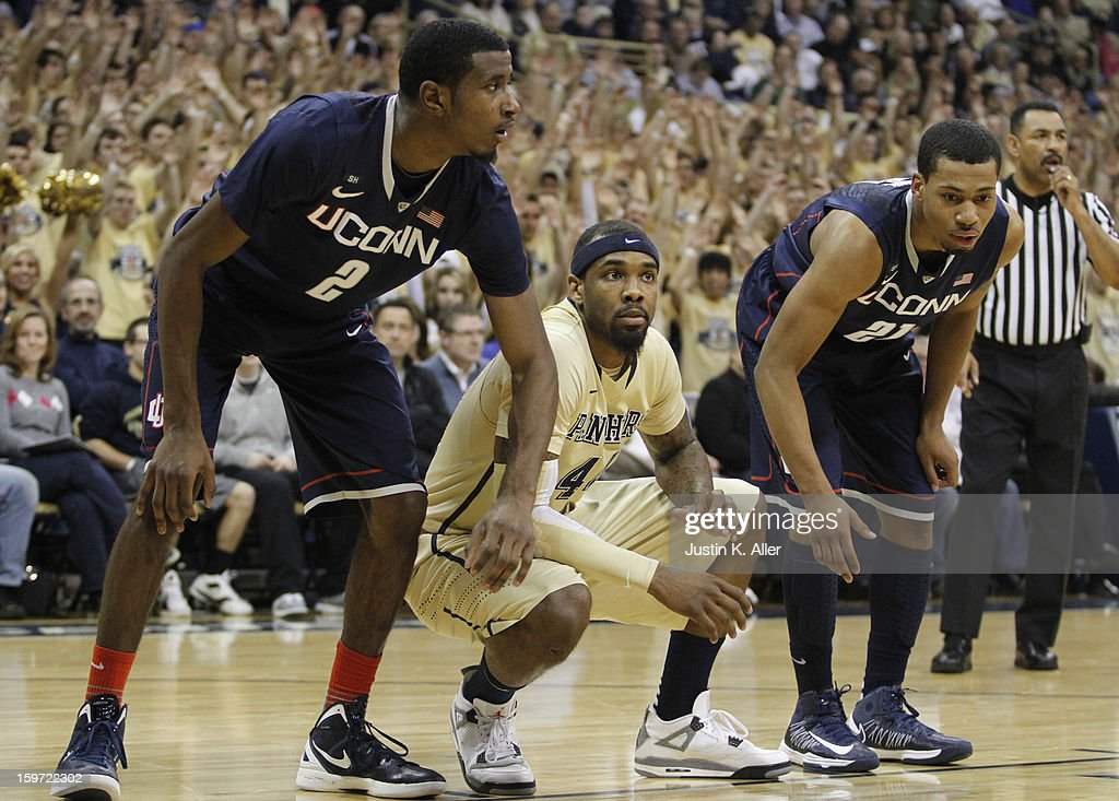 J.J. Moore #44 of the Pittsburgh Panthers prepares for a rebound against DeAndre Daniels #2 and Omar Calhoun #21 of the Connecticut Huskies at Petersen Events Center on January 19, 2013 in Pittsburgh, Pennsylvania.