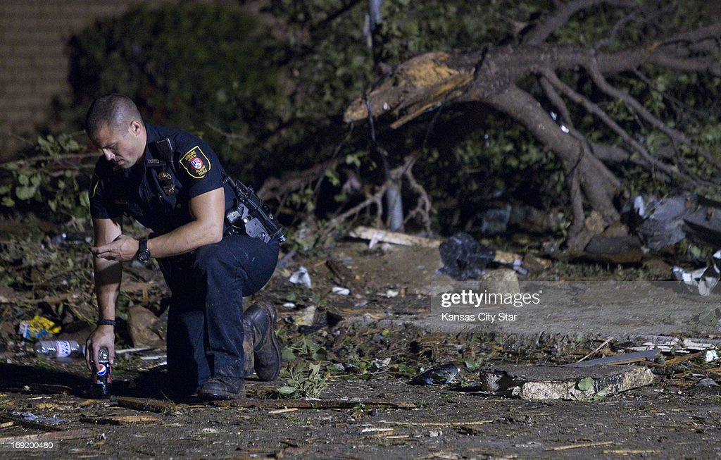 A Moore, Oklahoma, police officer checks his cell phone, as emergency crews continued searching in the early morning hours on Tuesday, May 21, 2013, in Moore, Oklahoma, after a tornado ripped through part of the town.