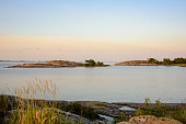 Sunset light over small skerries and sailboats moored at a small rocky island in the outer part of the archipelago of Stockholm, Sweden