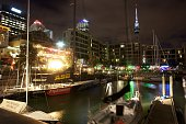 Moored yachts in Viaduct Basin at night time with Sky Tower in the background Auckland New Zealand Located in the heart of Auckland City Viaduct...