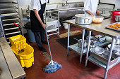 Two real food service professionals cleaning up a commercial kitchen. Promptly cleaning-up trash and debris in a restaurant or commercial kitchen is important for food safety and personal safety. A co