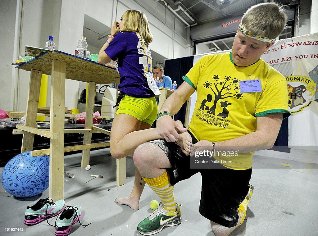 Moraler Matt Ross massages Lauren Killian's foot in the hallways of the Bryce Jordan Center during the Penn State IFC/Panhellenic Dance Marathon in State College, Pennsylvania, Sunday, February 17, 2013.