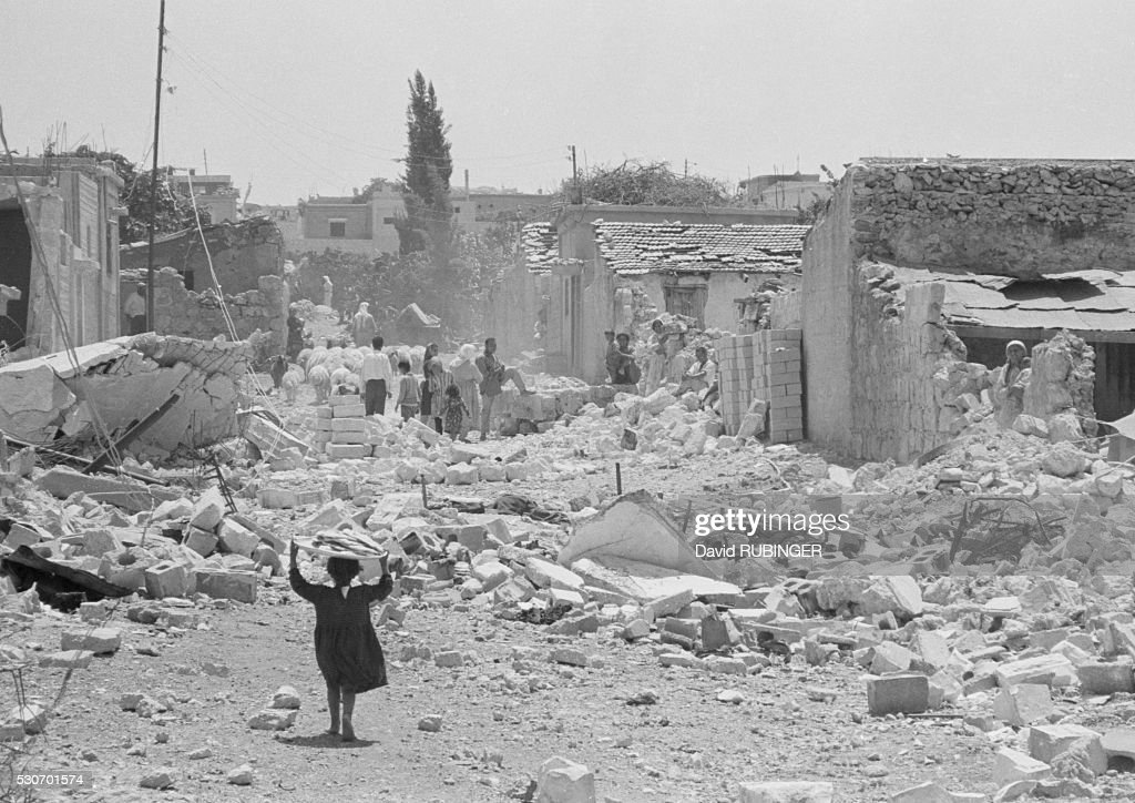 More of war's debris. This is Kalkilya after the Six Day War. The village is now on its long way back to recovery. A child carrying a tray of food on her head. The rocks can be cleaned and the shattered houses rebuilt. But the child?